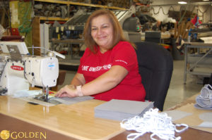 Golden employee sewing masks for Geisinger